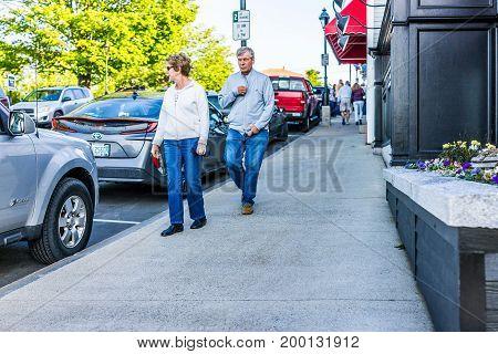 Bar Harbor USA - June 8 2017: Older couple walking on sidewalk during sunset in downtown village in summer