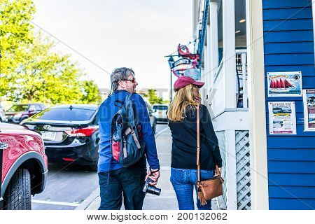 Bar Harbor USA - June 8 2017: Couple walking on sidewalk during sunset in downtown village in summer looking at restaurants