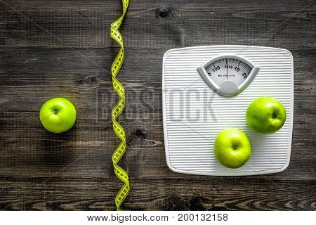 Lose weight concept. Bathroom scale, measuring tape, apples on wooden background top view.