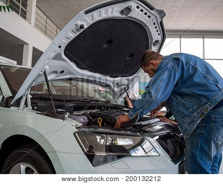 Voronezh, Russia - June 04, 2017: The man inspects the engine compartment of the new car