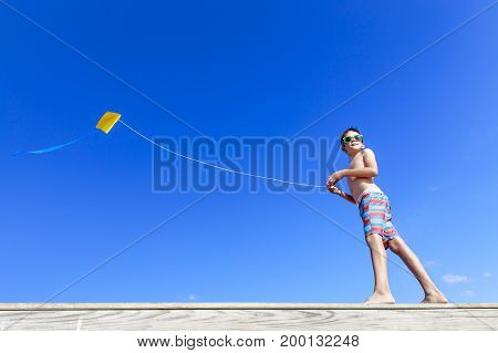 Boy with flying kite.  boy on the beach playing with a kite on the background of blue sky. Copy space for your text