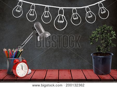 Digital composite of Desk foreground with blackboard graphics of light bulbs