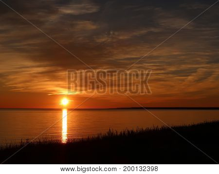 The path of the setting sun flames across Lake Michigan to a grassy sand dune on the south shore of the upper peninsula of Michigan.