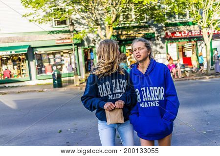 Bar Harbor USA - June 8 2017: Young girls people wearing Maine sweaters crossing main street in downtown village in summer by stores