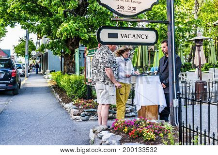 Bar Harbor USA - June 8 2017: Couple of people checking into hotel in downtown village in summer