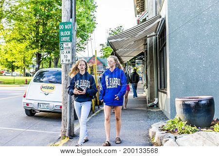 Bar Harbor USA - June 8 2017: Young girls people wearing Maine sweaters walking in downtown village in summer by stores