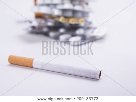 Cigarette on the white background against pills. Smoking ruins your health