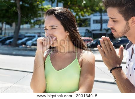 Caucasian woman crying after relationship difficulties with hispanic friend outdoor in the city in the summer
