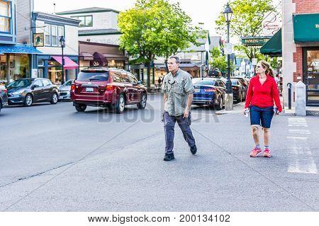 Bar Harbor USA - June 8 2017: People crossing sidewalk street in downtown village in summer on main road