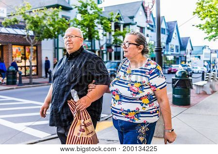 Bar Harbor USA - June 8 2017: Couple crossing sidewalk street in downtown village in summer on main road carrying food