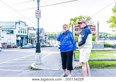 Bar Harbor USA - June 8 2017: Senior couple standing on sidewalk by oceanfront resort inn sign with waterfront in downtown village in summer