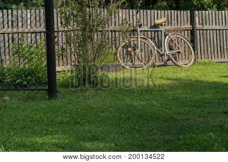 An old bicycle stands near a fence in the suburban area.