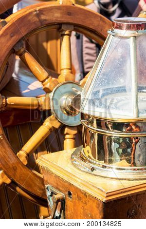 A wooden steering wheel ann vintage compass shine in the sunlight on a sightseeing sailboat in Maine.
