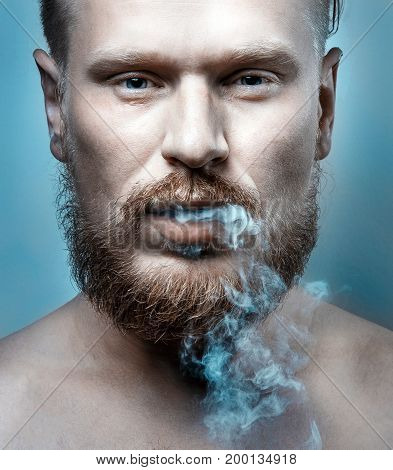 Portrait Of A Handsome Man With A Beard Cigarette Smoke Coming Out Of His Mouth Close-up. Harmful Habit Concept