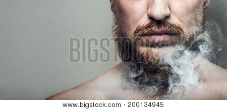 Portrait Of Man In A Club Of Cigarette Smoke. Harmful Habit And Harm To Health Concept