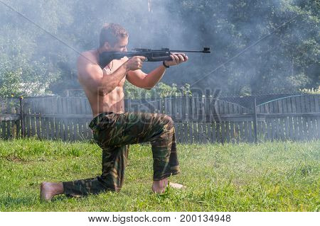 A Man Shoots A Target From A Pneumatic Gun. View Of A Person From The Side