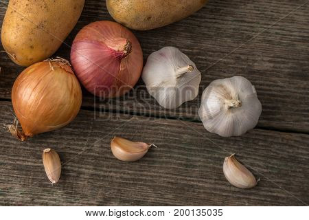 Garlic, Onion And Potatoes On An Old Table