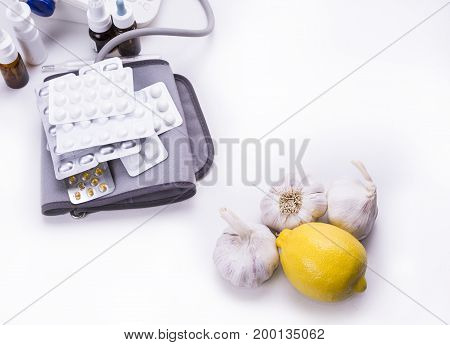 Lemon and garlic versus druga and pills on the white background