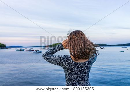 Young Woman Pointing To Boats On Edge Of Dock In Bar Harbor, Maine At Sunset