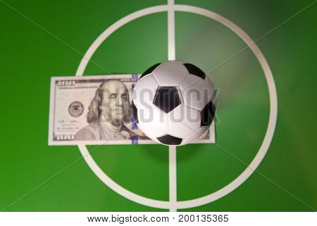 Sports and money concept - Toy soccer ball in a midfield in the center of the green field and the banknote in hundred dollars on a background