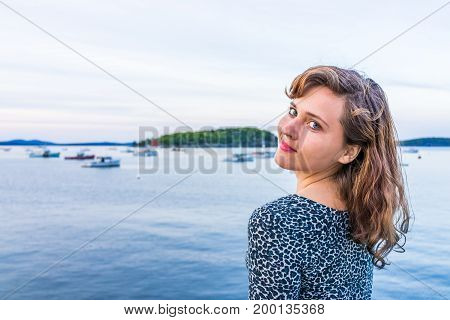 Young Happy Smiling Woman Sitting On Edge Of Dock In Bar Harbor, Maine Looking Over Shoulder