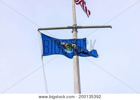 Closeup of blue Maine state flag on pole