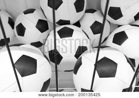 soccer balls in black and white metal sieve shelf