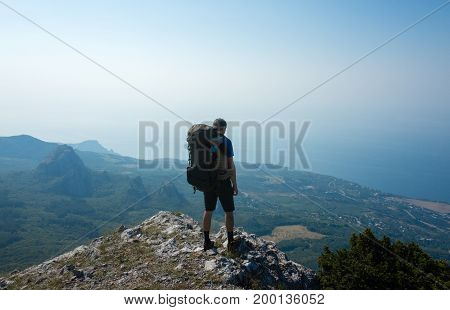 A young tourist with a backpack stands at the edge of the cliff and looks at the mountain landscape and the sea.