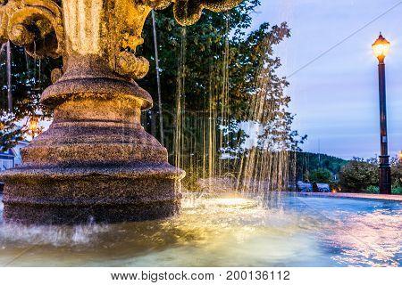 Closeup Of Splashing Water Fountain In Downtown Village Park During Evening Dark Night With Illumina