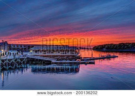 Bar Harbor USA - June 8 2017: Downtown village in summer during bright red sunset twilight with waterfront restaurant
