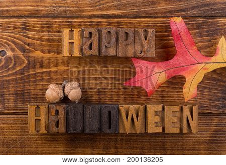Happy halloween sign with autumn leaf and acorns on a wood background