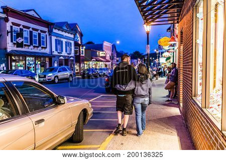 Bar Harbor USA - June 8 2017: Couple walking on sidewalk street by romantic Main road in downtown village during evening night
