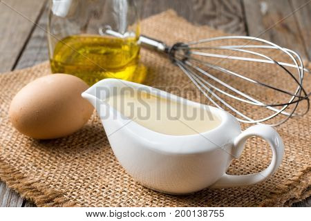 Fresh homemade mayonnaise on a wooden background