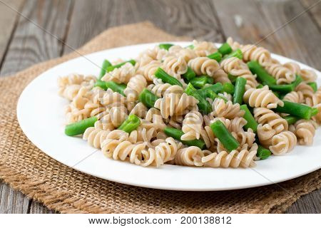 Whole wheat pasta with asparagus on a wooden background