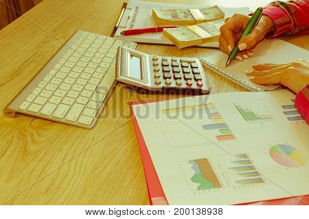 Young woman working in home sitting at desk using computer. Business grant and finances concept. Business woman working at the office - Retro color