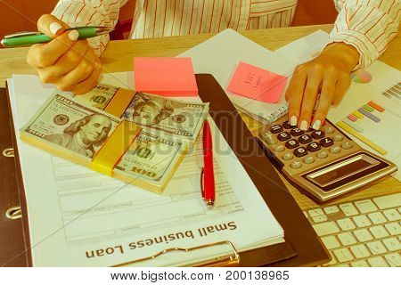 Female with Business plan calculator dollar banknote spreadshee and pen on the table. Young woman working in office sitting at desk using computer - Retro color