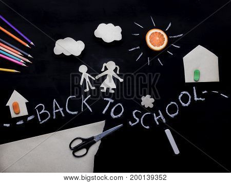 Back to school background with the child going to school. Children's creativity. Pencils and scissors on the table. Application on a blackboard. View from above