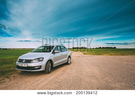 Gomel, Belarus - June 13, 2016: Volkswagen Polo Vento Car Parking On A Roadside Of Country Road On A Background Of Green Spring Fields Or Meadow In Sunny Day With A Beautiful Blue Sky