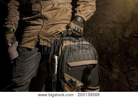 Man in storm jacket and tactical military gloves holding a backpack with travel gear on stone wall background.