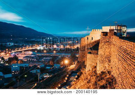 Gori, Shida Kartli Region, Georgia. Walls Of Gori Fortress And Cityscape In Evening Illumination Under Blue Sky. Travel Destination In Night Lights. Goris Tsikhe Is A Medieval Citadel