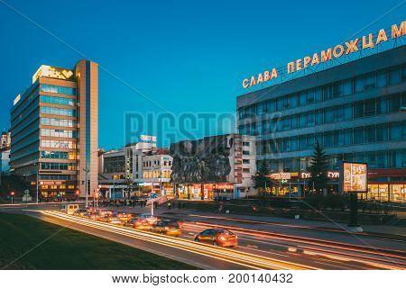 Minsk, Belarus - April 3, 2017: Evening Night Traffic Near Bas-relief of the Soviet era on old facade building On Illuminated Nemiga Street In Minsk, Belarus