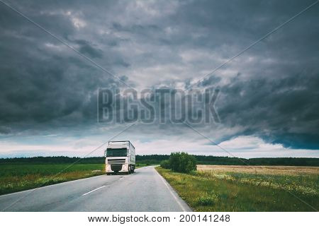 Truck, Tractor Unit, Prime Mover, Traction Unit In Motion On Country Road, Freeway In Europe. Cloudy Sky Above The Asphalt Motorway, Highway. Business Transportation Concept