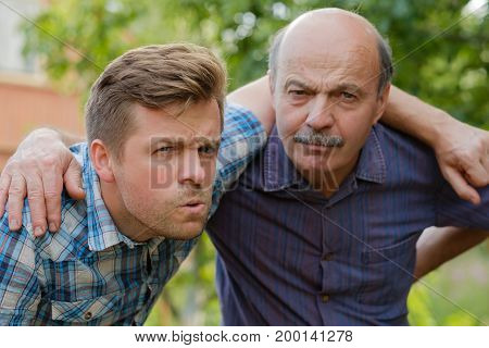 Portrait of doubting men. Dad and son look forward and frown. Negative emotion concept