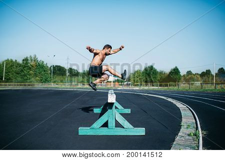 Professional male track and field athlete during obstacle race. Young athlete jumping over a hurdle during training on racetrack in athletics stadium