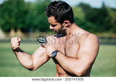 Sport and health. Young man with muscular body holding magnifying glass.