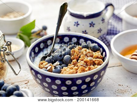 Granola with natural yogurt, fresh blueberries, nuts and honey in a ceramic bowl on a white wooden table, close up. Delicious breakfast or dessert.  Healthy eating concept.