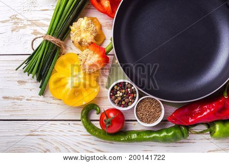 Various Vegetables Ingredients On Wooden Table Around Frying Pan