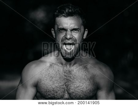 Screaming man with well trained body, tense face, black and white photo