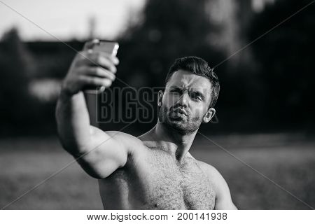 Half body shot of a handsome young man using cell phone to take photo