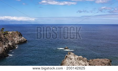 Seascape. A sailboat with white sails floats along the rocky coast of Los Gigantos (Tenerife Spain)